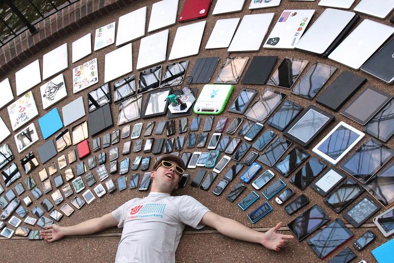 Man liggend op de grond tussen heel veel mobiele apparaten